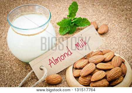 Almond milk with almond tag paper on a wooden table