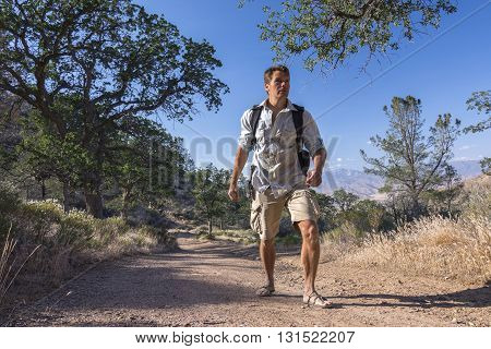 Rugged Caucasian outdoorsman hikes with backpach and sandals on dirt road in California mountains