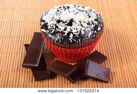 Homemade delicious fresh baked chocolate muffins with desiccated coconut in red silicone cups and pieces of chocolate concept for dessert