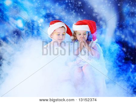 Beautiful little angelic children in a smoke at a stellar sky.