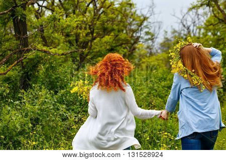 Best friends forever. Girlfriends strolling hand in hand. BFF. Walk. The girl on a head a wreath of wildflowers. Photos from behind. People are not recognizable