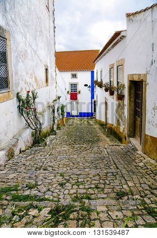 Obidos Portugal a medieval city encircled by a fortified wall. Its streets squares walls and its massive castle have turned the picturesque village into a preferred tourist attraction in Portugal.