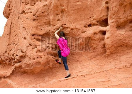 The young woman at Valley of Fire State Park, USA. The Valley of Fire State Park is the oldest state park in Nevada, USA and was designated as a National Natural Landmark in 1968.