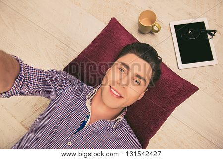 Selfie Of Handsome Happy Man Lying On Floor With Tablet And Cup Of Tea