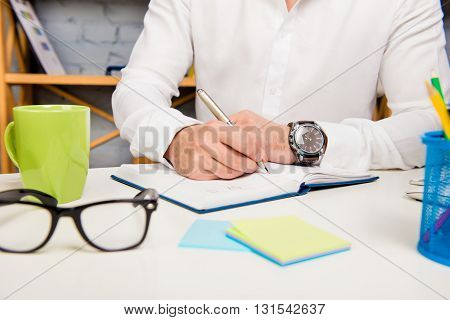 Close up photo of businessman writting plan for day in daybook