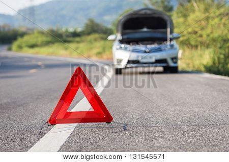 Red Emergency Stop Sign And Broken Car On The Road
