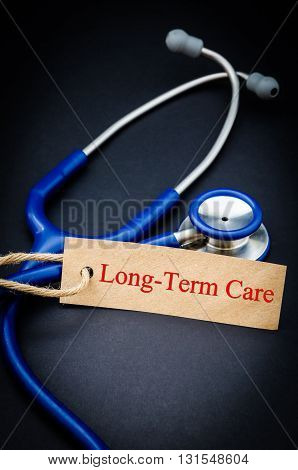 Long term care in paper tag with stethoscope on black background - health concept. Medical conceptual