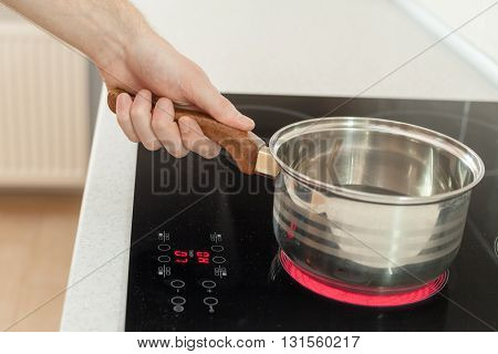 Hand holding a saucepan in modern kitchen with induction stove