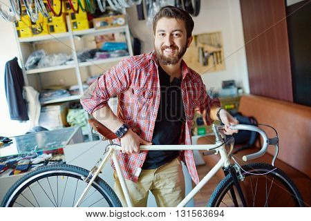 Portrait of a man with bicycle in sports shop