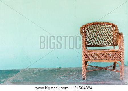 Wicker chair on a turquoise wall, India