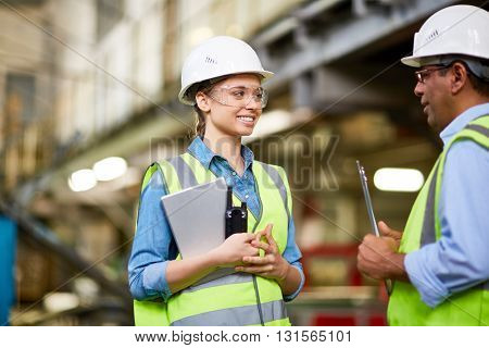 Technician inspecting a young trainee at factory
