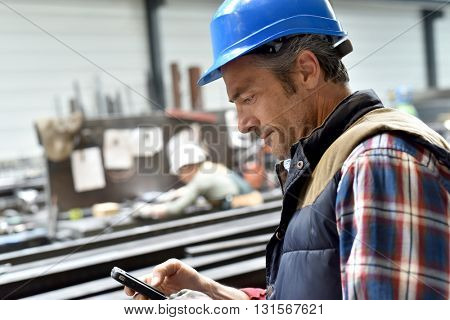 Man in steelwork factory using smartphone