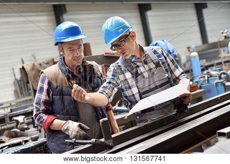 Engineers working on project in metallurgy workshop