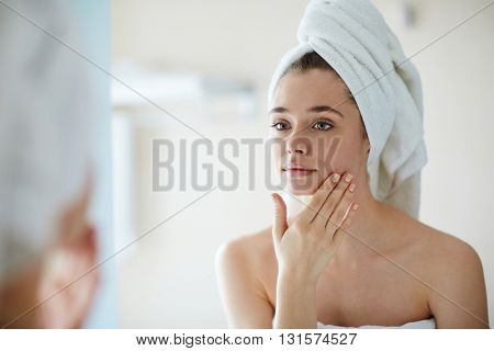 Young woman looking at mirror in bathroom and pampering her face
