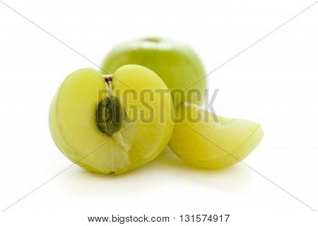 One whole, half and slice of Organic Indian gooseberry or Amla (Phyllanthus emblica) with visible seed isolated on white background.