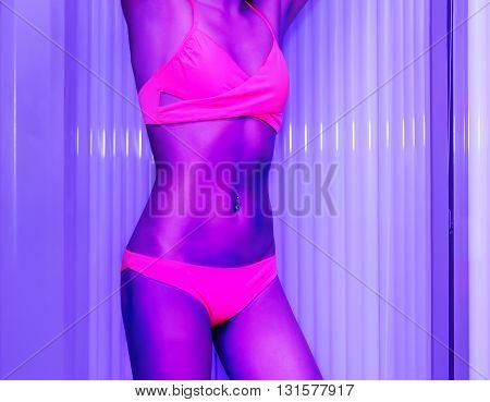Slim Young Woman Standing In Solarium Getting Sun Tan