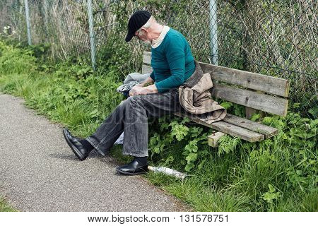 Homeless Man Gathering Stuff On Outdoor Bench.