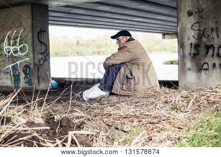 Senior wanderer with hat sitting under bridge.