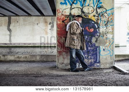 Wanderer Standing Against Concrete Pillar Under Bridge.