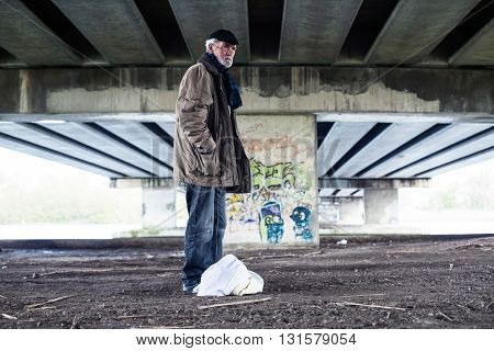 Lost Homeless Man Standing With Bag Under Bridge.