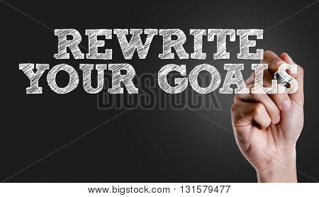 Hand writing the text: Rewrite Your Goals