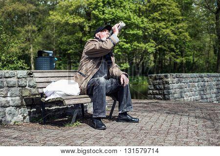 Wanderer On Bench In Park Drinking From Bottle.