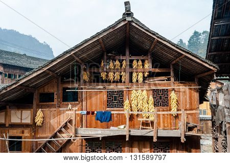 Traditional wooden house with yellow corn cobs hanged on the wall in Langde Miao Village Guizhou China