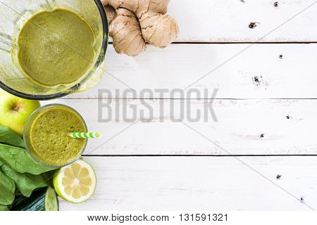 Healthy green detox in glass on white wood