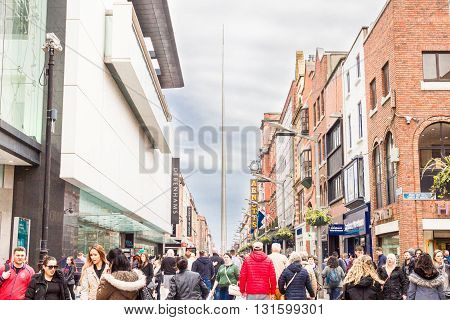 DUBLIN, IRELAND - MAY 6, 2016: People walking in the Henry Street with the Spire on the background. In O'Connell Street, the monument has 121.2 m high and is also know as Spike and Monument of Light.