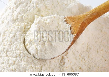 wooden spoon of wheat flour - close up