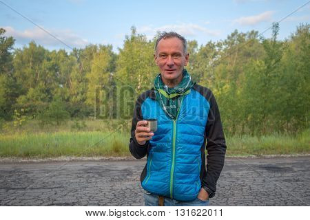 Portrait of a tired smiling traveler with cup of coffee standing on the old road on the background of the green trees early in the morning after a sleepless night in the journey.