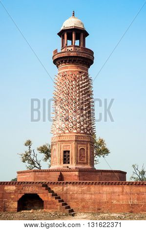 Hiran Minar. Red sandstone minaret decorated with stone elephant tusks Fatehpur Sikri India