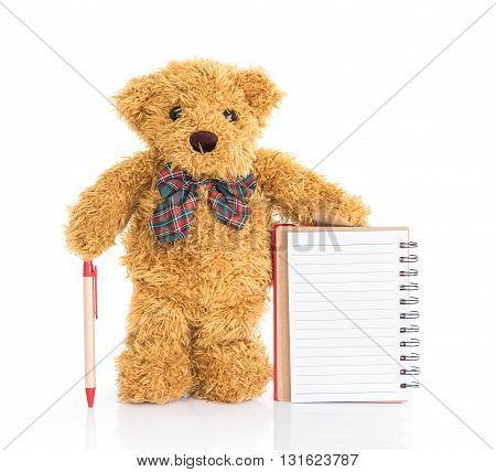 Teddy bear with pen and blank notebook on white background