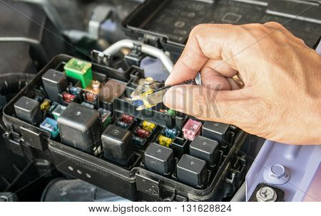 Auto mechanic checking a car fuse.car, fuse, automotive, electronics,