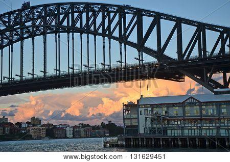 Sydney Harbour Bridge frames orange and pink clouds at dusk