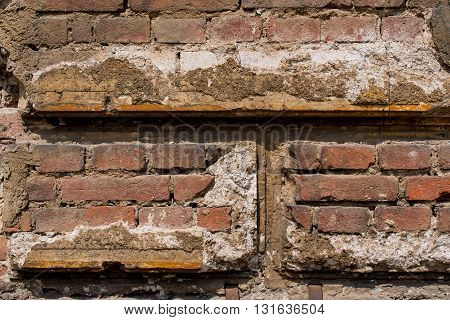 reddish brown brick wall with damaged plaster - background texture