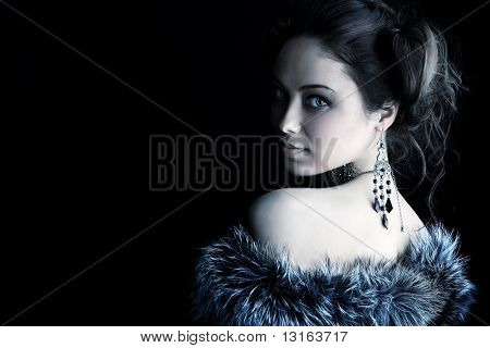 Portrait of a beautiful woman over black background..