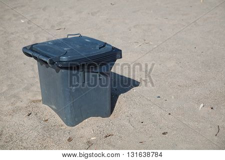 Trashcan at a beach in burried in the sand