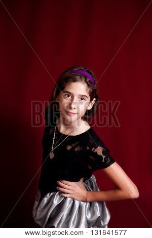 Studio portrait of a young, tween girl on a red background.  She confidently leans towards the camera with a knowing expression on her face.