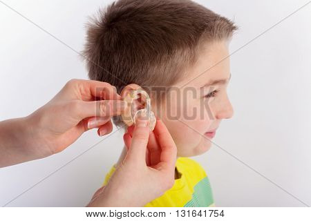 Audiologists hand showing a hearing aid before inserting it into a young boys ear. Focused on the hands and the hearing aid.