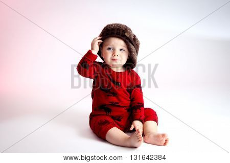 A sly looking baby boy sits with a side tipped hat.  He is looking off camera with a confident and slightly cocky look on his face. He is wearing red pajamas with moose print and a knit visor tam style hat.