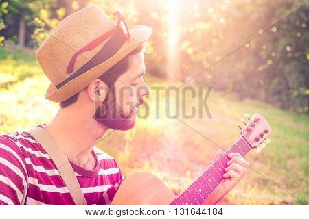 Young man playing guitar in city park on sun rays background - Handsome hippie style guitarist engrossed on music outdoors - Concept of freedom relaxation and passion - Vintage look and sun flare