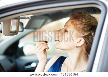 Blonde woman applying make-up in a car.