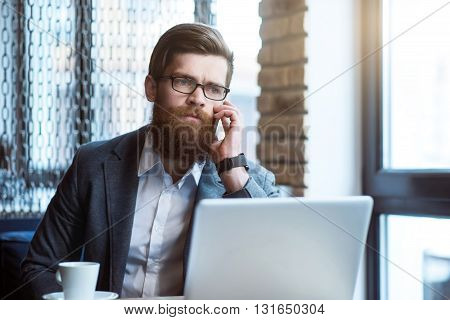 Do not despair. Pleasant cheerless bearded serious man sitting at the table  while talking on cell phone