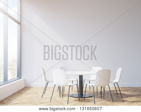 Round table and chairs in conference room interior with wooden floor blank wall and window with city view. Mock up 3D Rendering