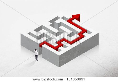 Solution concept with red arrow going through maze and thoughtful businessman on concrete background