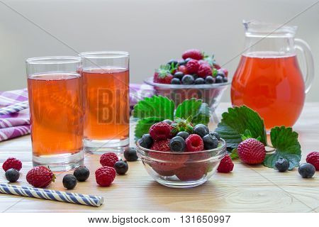 Left two glasses of compote of raspberries strawberries blueberries near bowl with berries right carafe compote on a light wooden background scattered berries. Fresh berries compote. Horizontal.