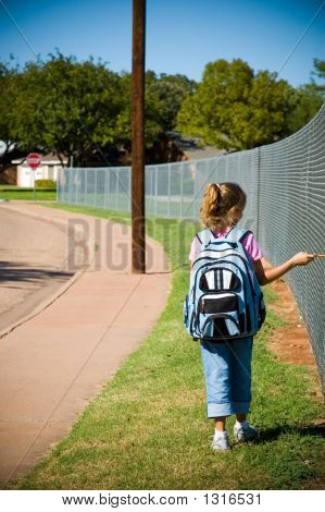 young girl walking by school yard on first day of school with backpack and pencil poster