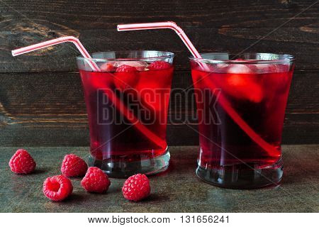 Raspberry Fruit Drinks In Glasses With Bendy Straws Over A Dark Background