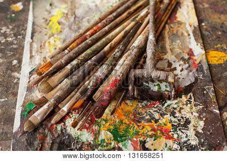Art materials. Different bedraggled used brushes on gray sloppy surface